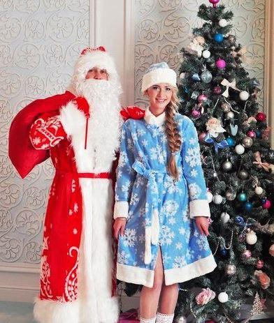 Дед Мороз и Снегурочка стоят рядом с елкой.